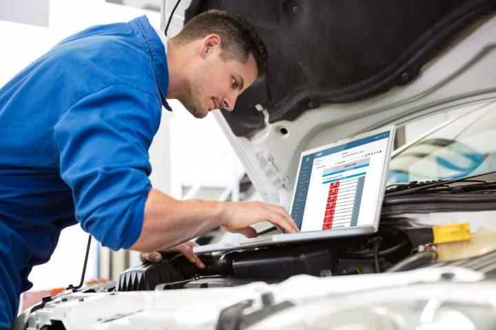 mecânico com roupa azul usando notebook apoiado em uma estrutura de veículo